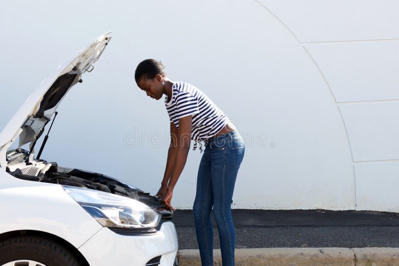 Giovane donna afroamericana che guarda sotto il cappuccio dell'automobile ripartita fotografia stock libera da diritti