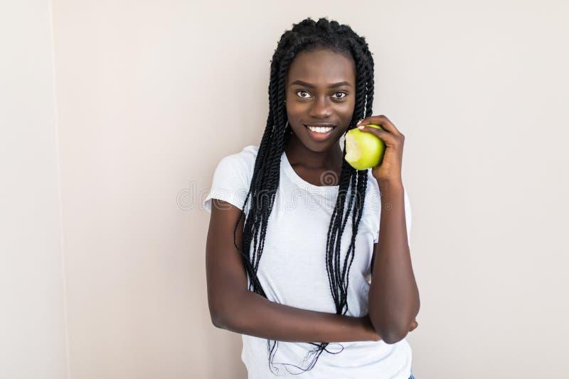 Giovane donna afroamericana che mangia mela verde isolata fotografia stock