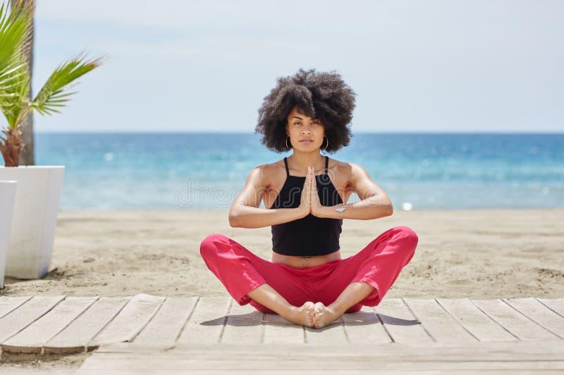 Giovane donna afroamericana che medita su spiaggia fotografie stock libere da diritti