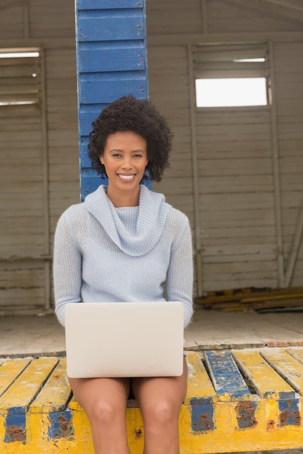Giovane donna afroamericana che per mezzo del suo computer portatile alla capanna della spiaggia fotografia stock libera da diritti