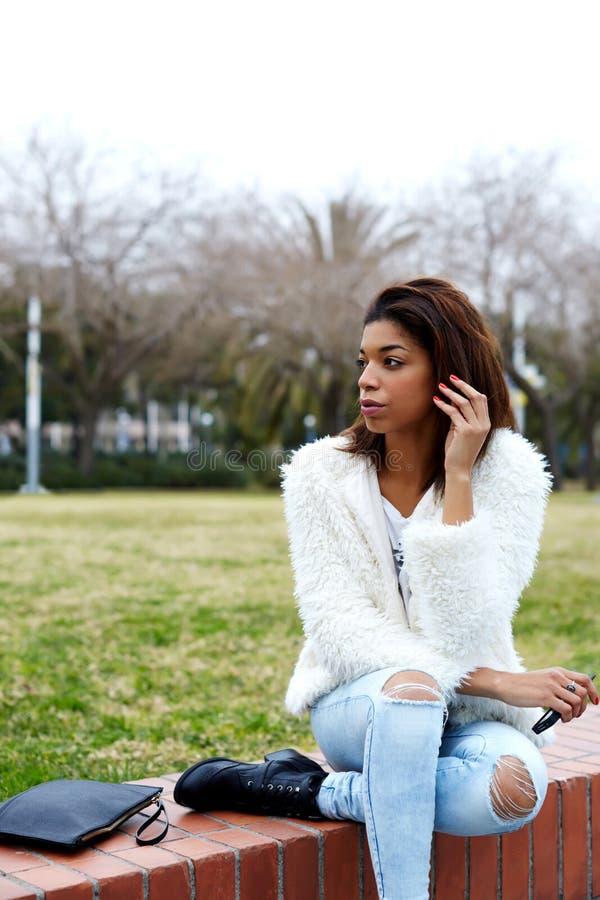 Giovane donna afroamericana che si siede nel bello distogliere lo sguardo del parco fotografie stock