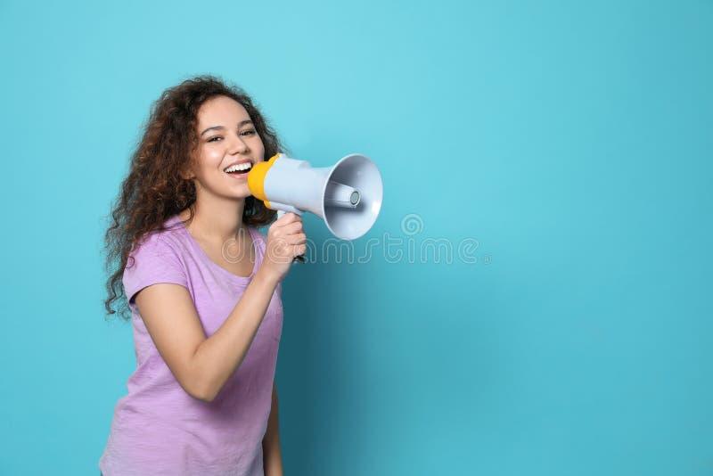 Giovane donna afroamericana con il megafono sul fondo di colore fotografia stock libera da diritti