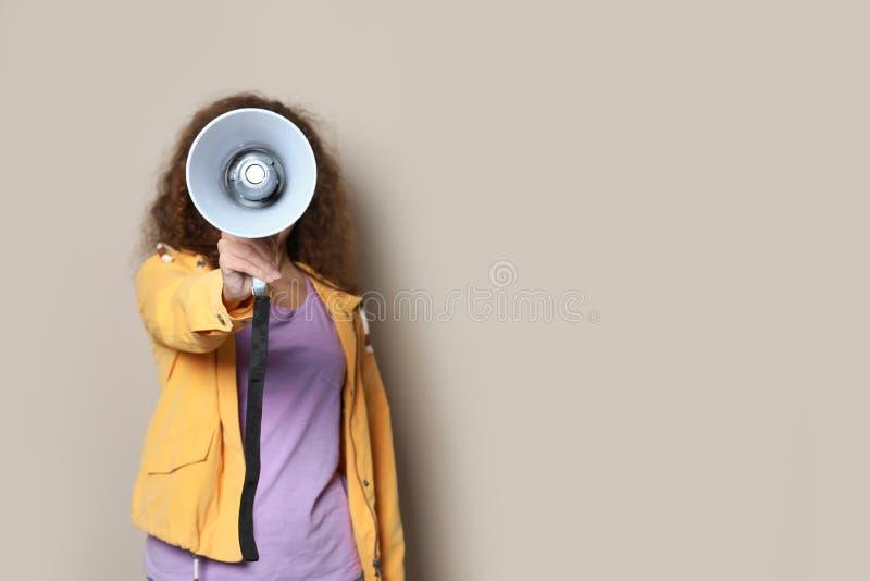 Giovane donna afroamericana con il megafono sul fondo di colore fotografia stock
