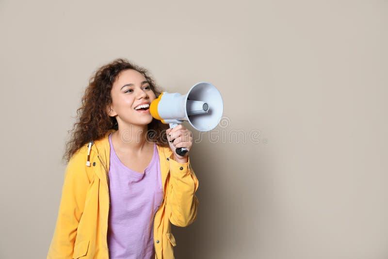Giovane donna afroamericana con il megafono sul fondo di colore immagine stock libera da diritti
