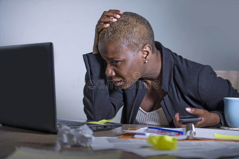 Giovane donna afroamericana disperata e sollecitata di affari che lavora allo scrittorio del computer portatile allo sforzo di so fotografia stock