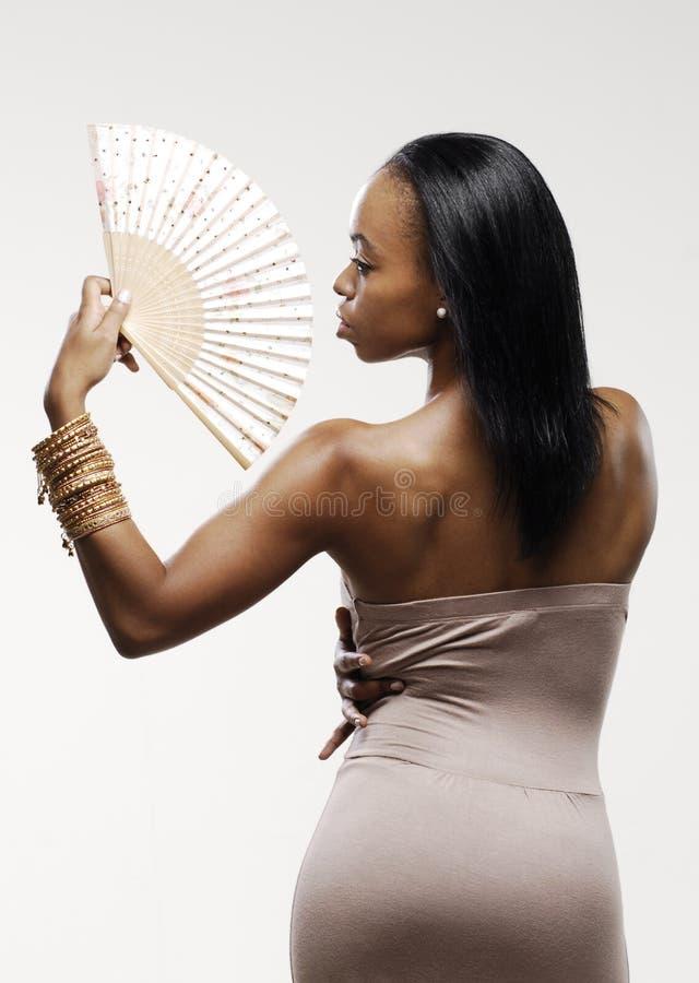 Giovane donna afroamericana elegante che posa e che tiene un fan immagini stock libere da diritti
