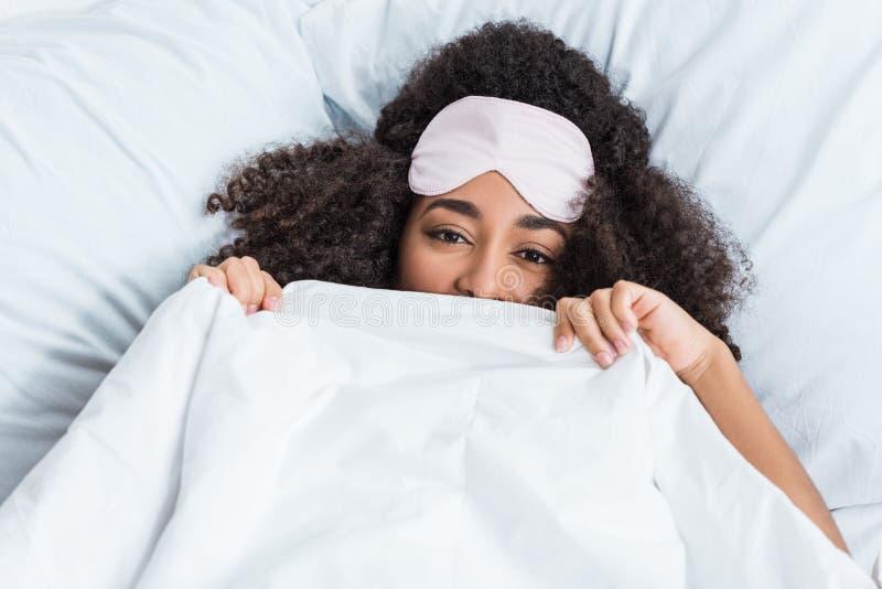 Giovane donna afroamericana felice con la benda sul fronte della copertura della fronte dalla coperta e porre a letto durante la  immagini stock libere da diritti
