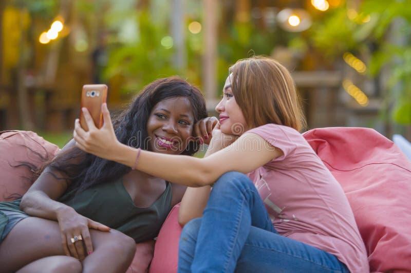 Giovane donna afroamericana nera felice e bella che gode delle feste alla località di soggiorno tropicale con l'amica asiatica ch fotografia stock libera da diritti