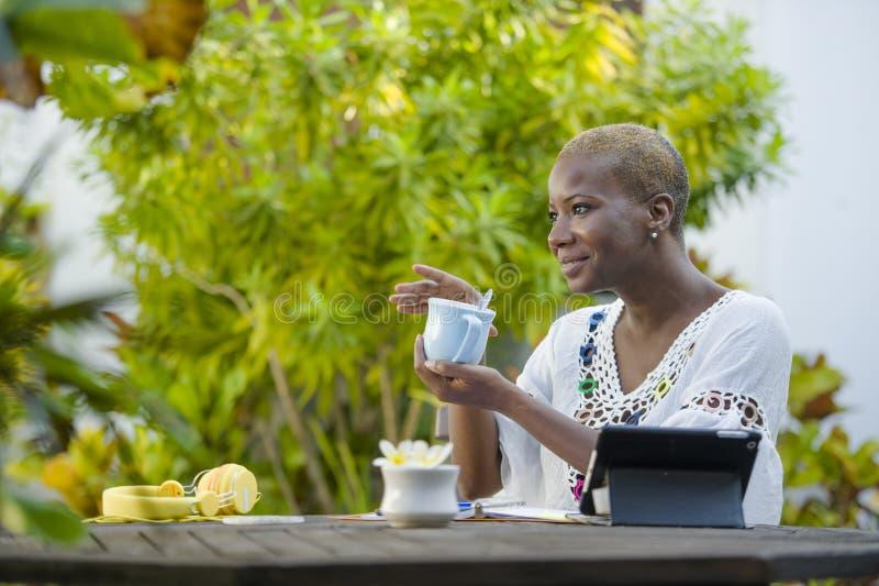 Giovane donna afroamericana nera felice ed attraente che lavora con la compressa all'aperto al tè bevente rilassato o al caffè de fotografie stock libere da diritti