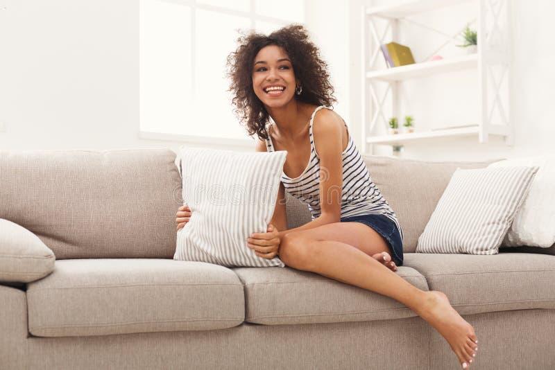 Giovane donna afroamericana sorridente sullo strato beige fotografia stock libera da diritti