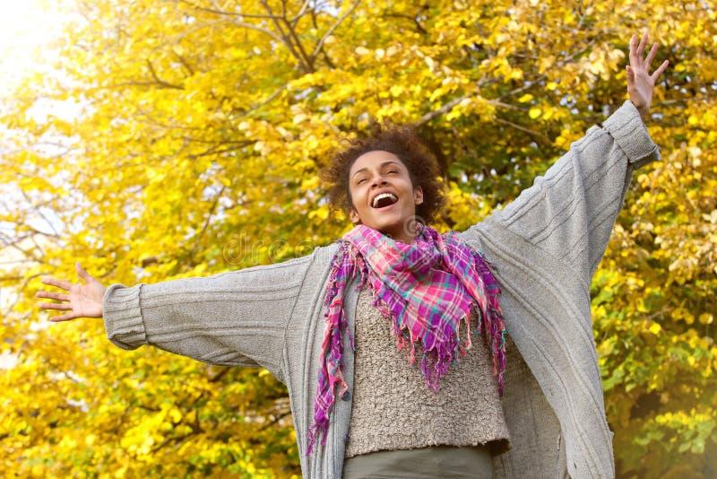 Giovane donna afroamericana spensierata con le armi stese fotografie stock