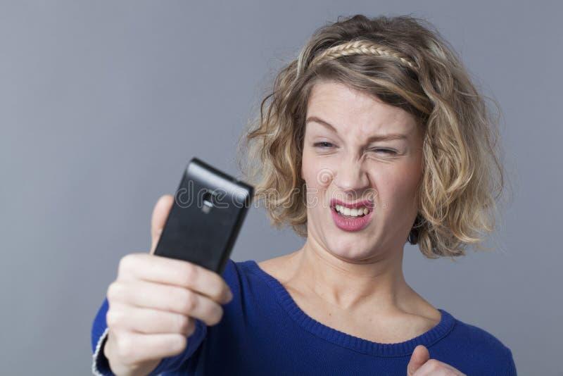 Giovane donna aggrottante le sopracciglia che aborre prendendo i selfies fotografia stock