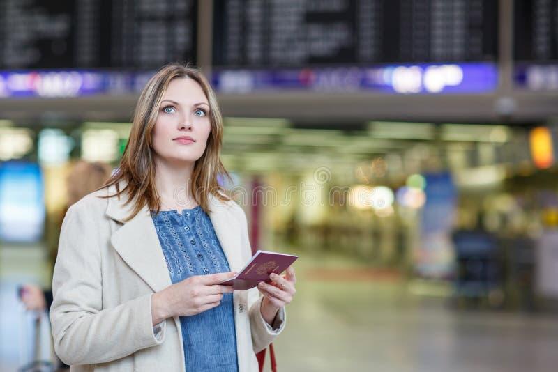 Giovane donna all'aeroporto internazionale, controllante bordo elettronico immagine stock libera da diritti