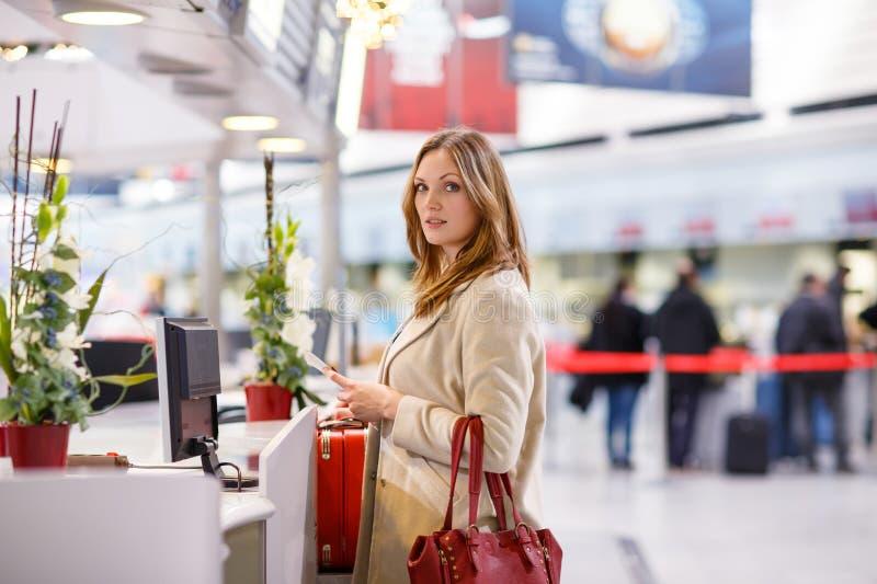 Giovane donna all'aeroporto internazionale, controllante bordo elettronico immagine stock