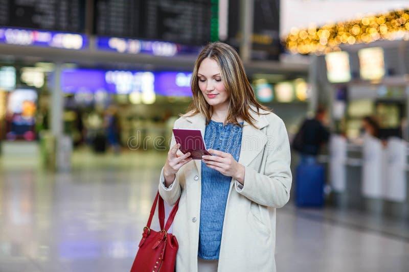 Giovane donna all'aeroporto internazionale, controllante bordo elettronico fotografie stock