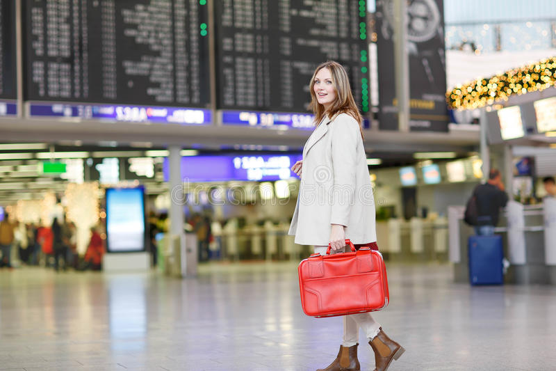 Giovane donna all'aeroporto internazionale, controllante bordo elettronico fotografia stock libera da diritti