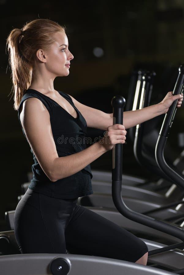 Giovane donna all'esercitazione di ginnastica Funzionamento sulla macchina immagine stock