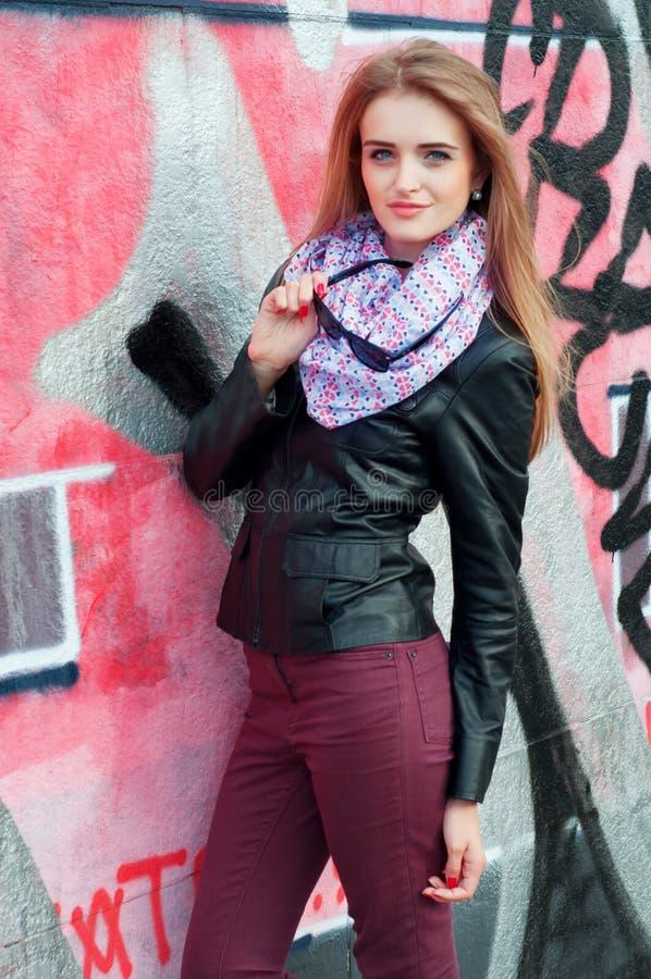 Giovane donna alla moda in bomber ed occhiali da sole neri immagine stock