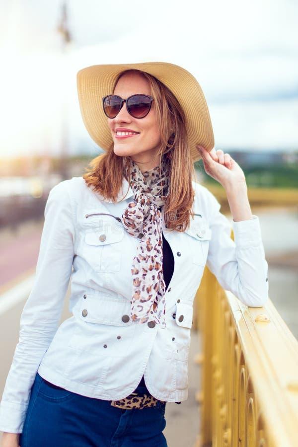 Giovane donna alla moda in cappello che posa sul ponte fotografia stock libera da diritti