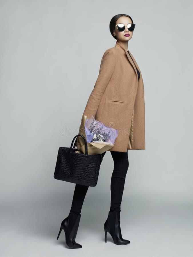 Giovane donna alla moda in cappotto beige fotografie stock