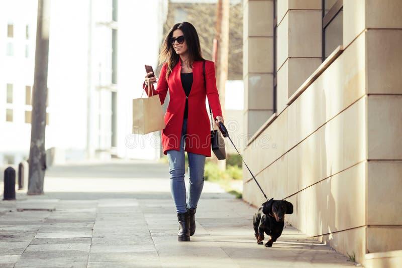 Giovane donna alla moda che cammina con il suo piccolo cane mentre mandando un sms con il suo smartphone sulla via nella città fotografie stock libere da diritti