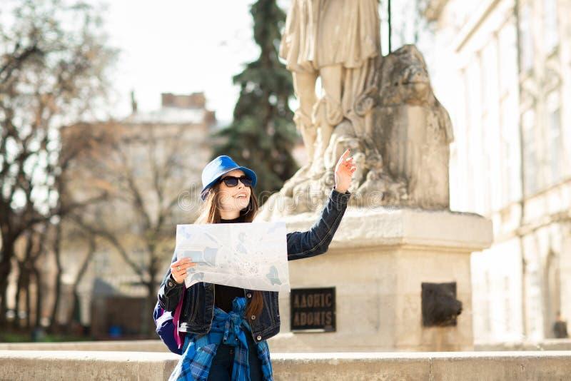 Giovane donna alla moda che cammina sulla vecchia via della citt?, sul viaggio con lo zaino e sul cappello blu L'Ucraina, Lviv fotografie stock