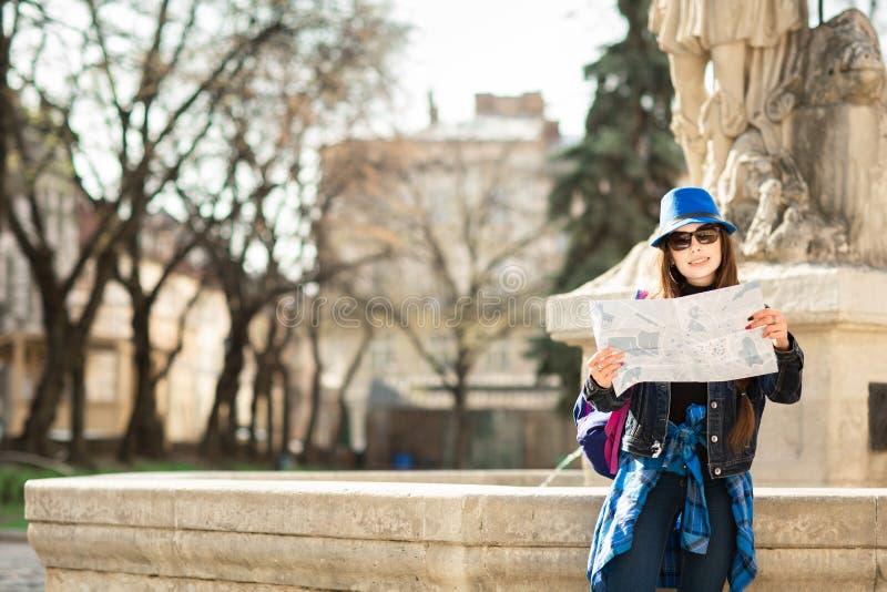 Giovane donna alla moda che cammina sulla vecchia via della citt?, sul viaggio con lo zaino e sul cappello blu L'Ucraina, Lviv immagine stock libera da diritti