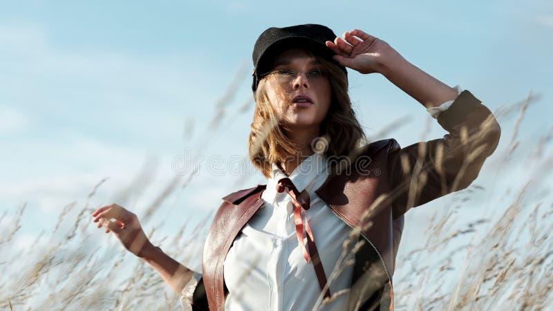 Giovane donna alla moda che posa contro il cielo fotografia stock