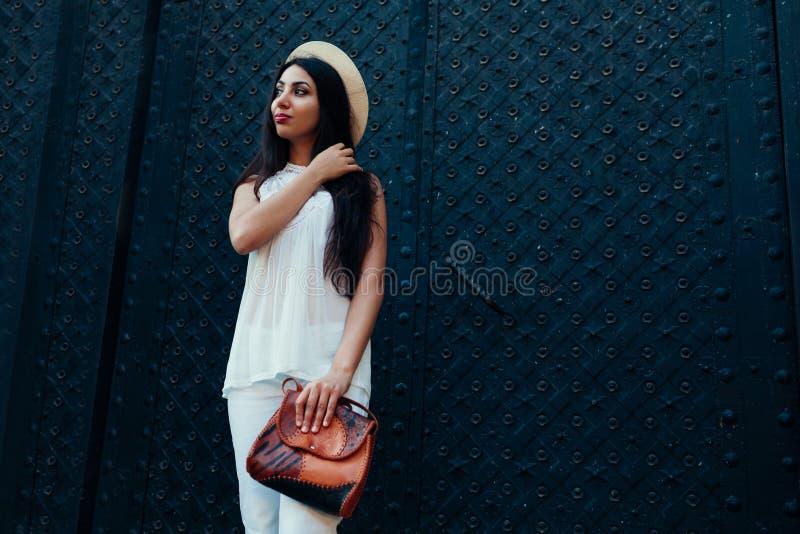 Giovane donna alla moda che posa contro le porte antiche nere fuori Attrezzatura di estate Bello Smiling di modello immagini stock