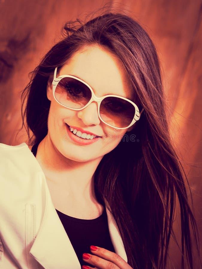 Giovane donna alla moda che posa durante il giorno soleggiato immagine stock