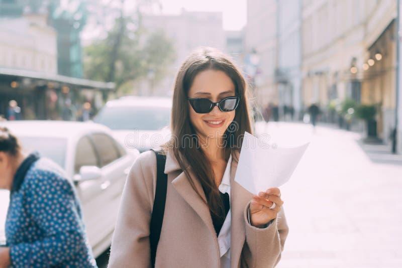 Giovane donna alla moda che posa alla via e che esamina macchina fotografica immagine stock libera da diritti
