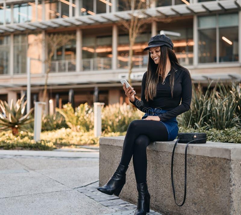 Giovane donna alla moda che si siede con la borsa dell'imbracatura che esamina il suo Mo fotografie stock libere da diritti