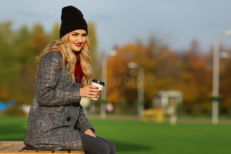 Giovane donna alla moda che sorride con il caffè in un parco fotografia stock