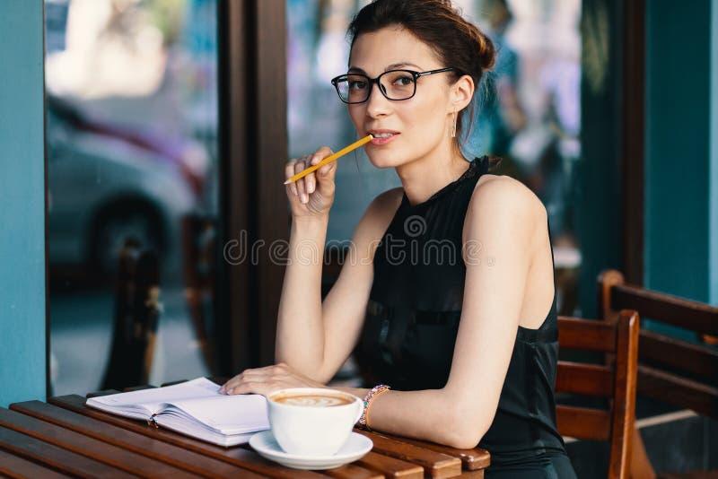 Giovane donna alla moda con i vetri alla moda che si siedono alla tavola nel CAM fotografia stock libera da diritti