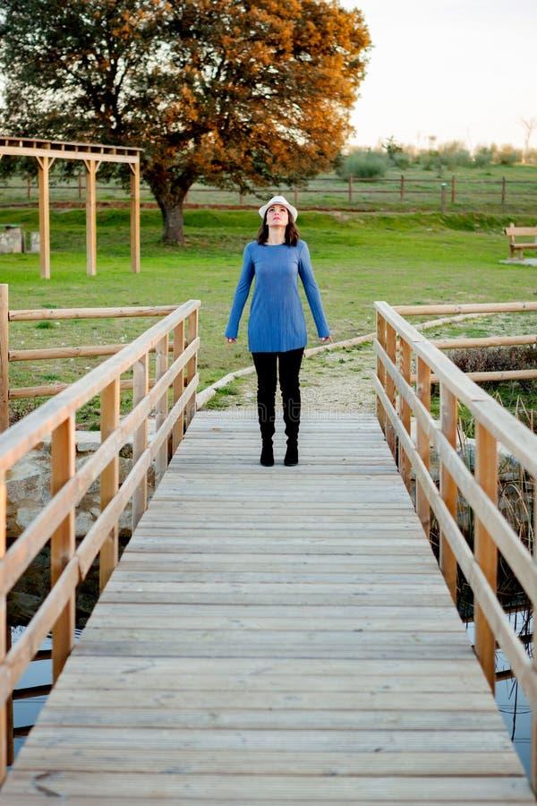 Giovane donna alla moda con il cappello del whithe su un ponte di legno fotografia stock