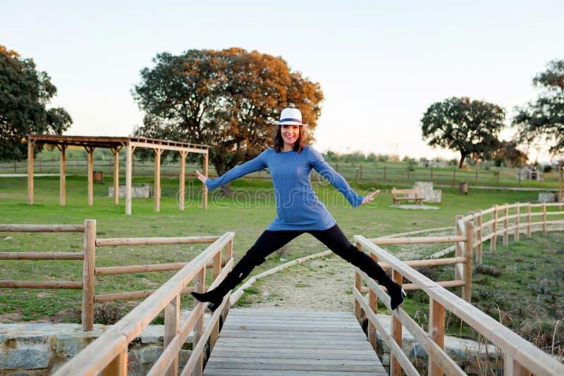 Giovane donna alla moda con il cappello del whithe su un ponte di legno immagine stock