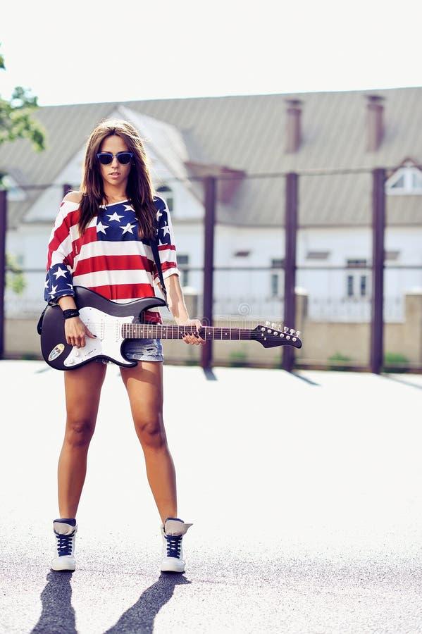 Giovane donna alla moda con il ritratto all'aperto di modo della chitarra immagine stock libera da diritti