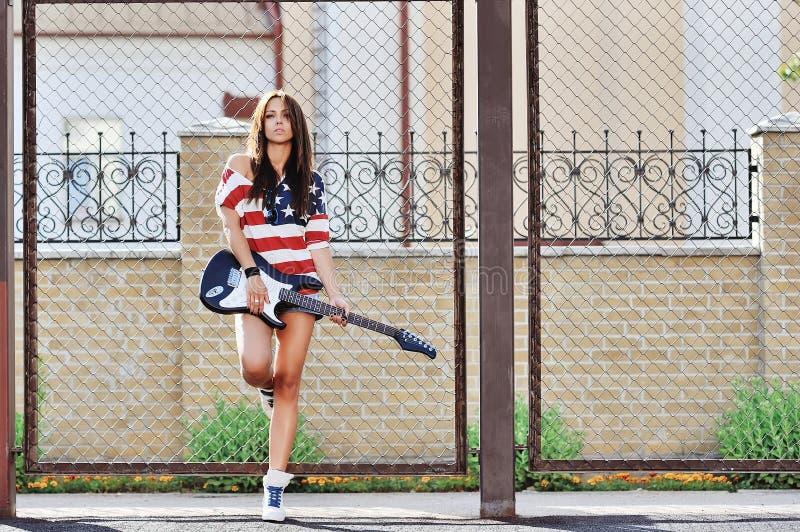 Giovane donna alla moda con il ritratto all'aperto di modo della chitarra immagini stock