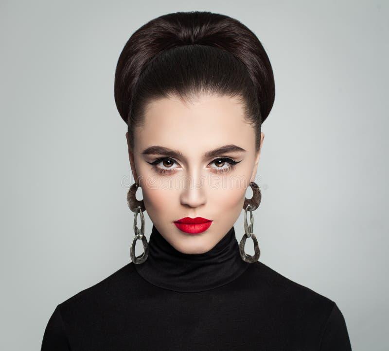 Giovane donna alla moda con la pettinatura del panino dei capelli fotografie stock libere da diritti