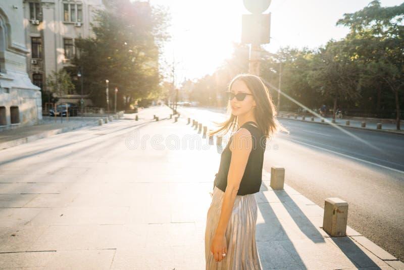 Giovane donna alla moda dei pantaloni a vita bassa che cammina sulla via fotografia stock