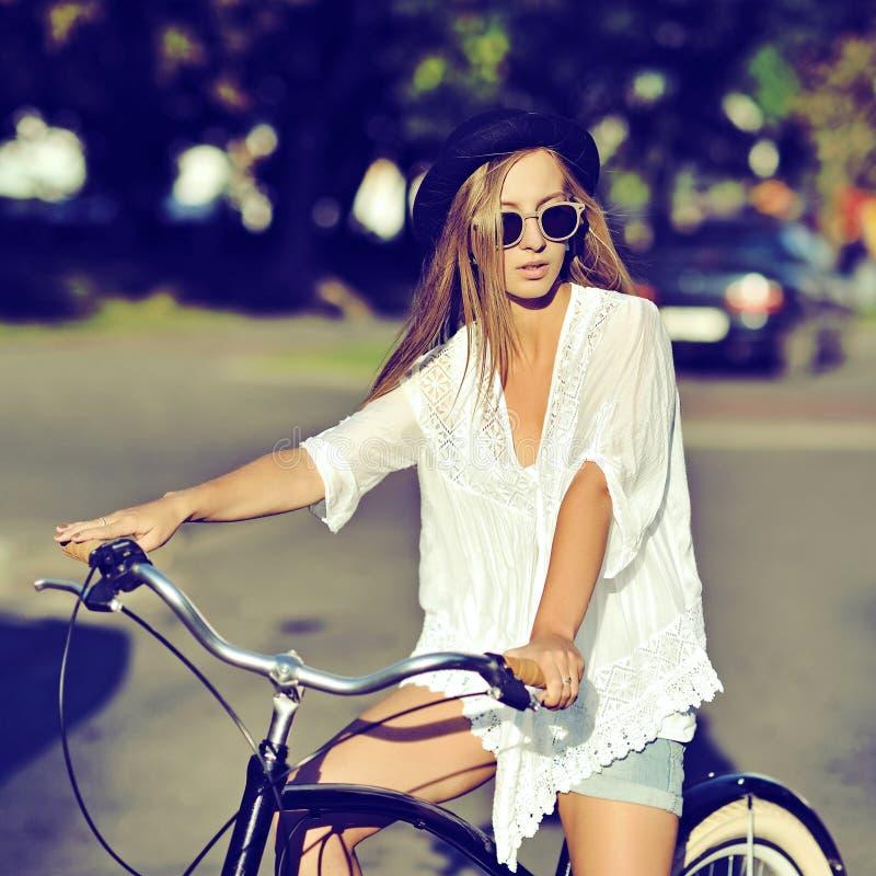 Giovane donna alla moda dei pantaloni a vita bassa su una retro bicicletta Modo esterno immagini stock