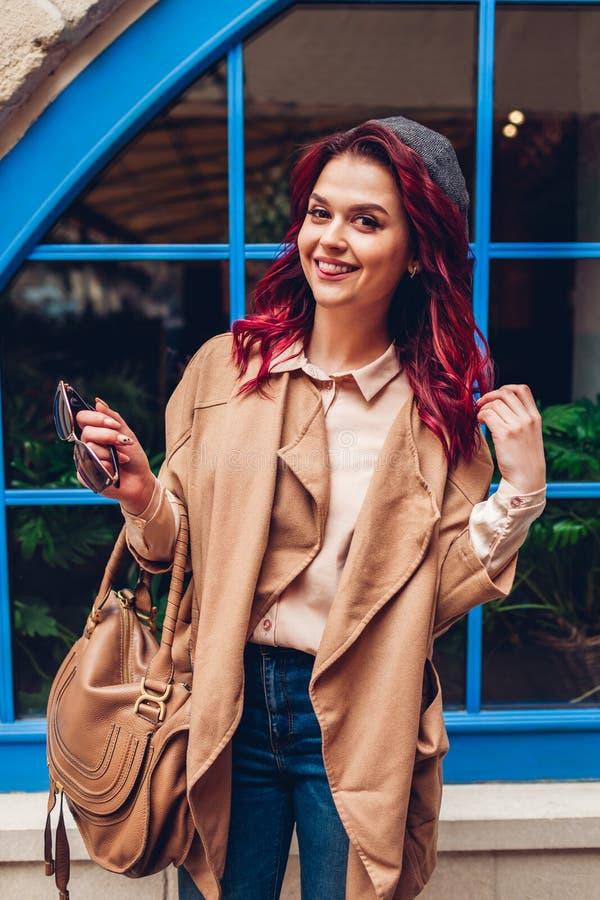 Giovane donna alla moda divertendosi all'aperto Attrezzatura alla moda di autunno Bella lingua di mostra di modello felice immagine stock libera da diritti