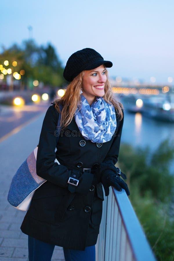 Giovane donna alla moda felice in cappuccio di inverno che cammina alla sera i immagini stock