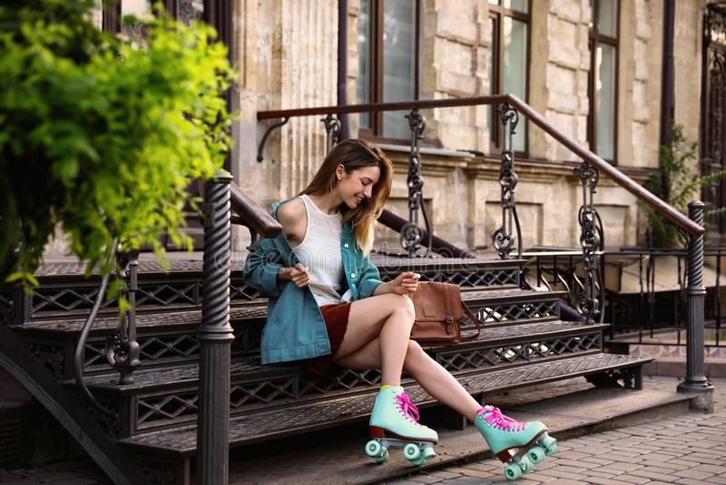 Giovane donna alla moda felice con i pattini di rullo d'annata e borsa che si siede sulle scale immagini stock