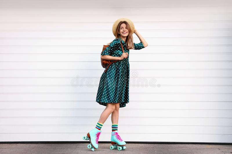 Giovane donna alla moda felice con i pattini di rullo d'annata, il cappello e lo zaino vicino alla porta bianca del garage immagine stock