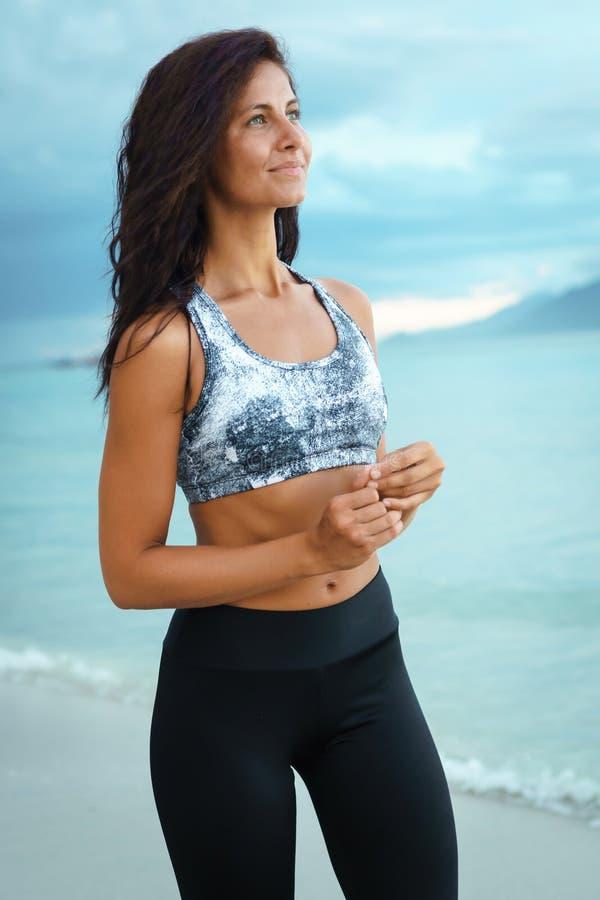 Giovane donna alla moda felice di sport che posa sulla riva di mare fotografia stock