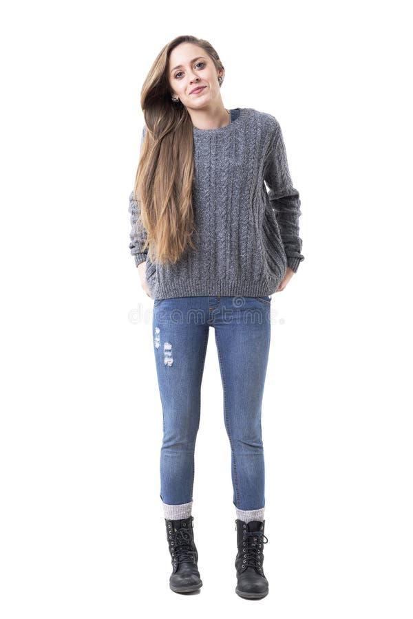 Giovane donna alla moda funky fresca in maglione grigio e jeans che posano con le mani in tasche della parte posteriore immagini stock