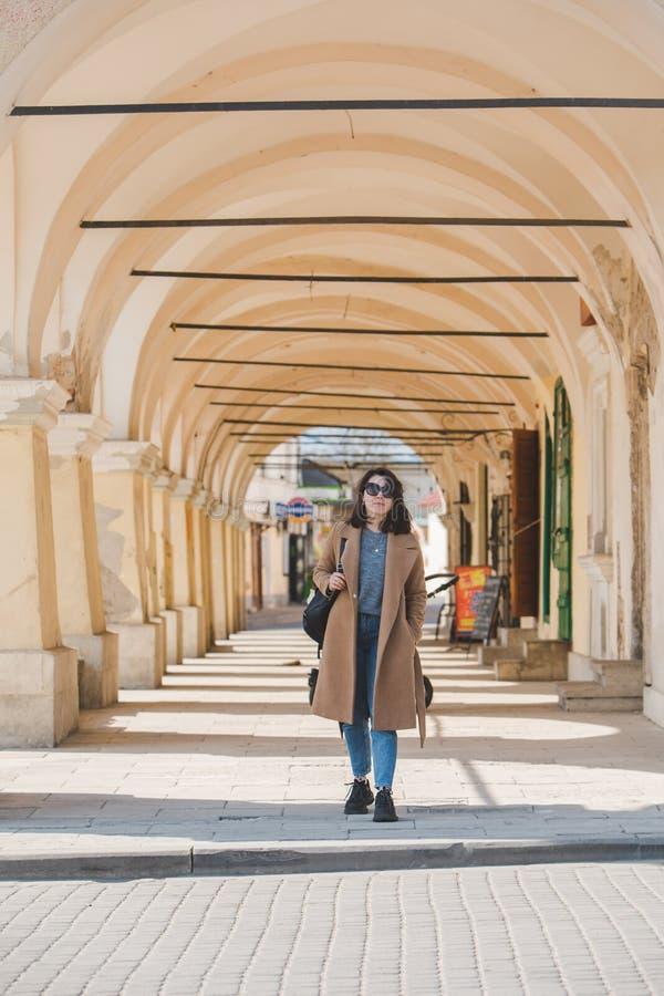 Giovane donna alla moda graziosa che cammina in cappotto marrone dalla via fotografia stock libera da diritti