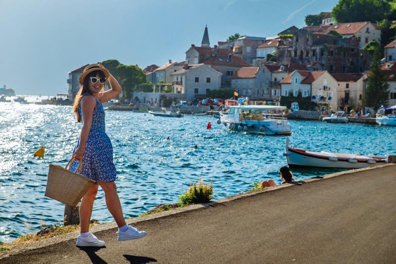 Giovane donna alla moda graziosa che cammina dalla banchina della città mare e montagne su fondo fotografia stock