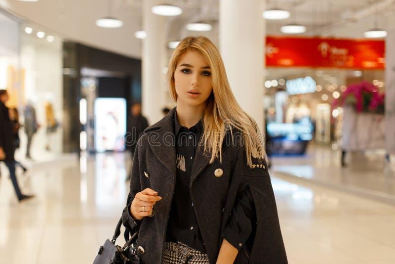 Giovane donna alla moda graziosa con capelli biondi in un cappotto grigio d'avanguardia con una borsa alla moda di cuoio in una b immagine stock
